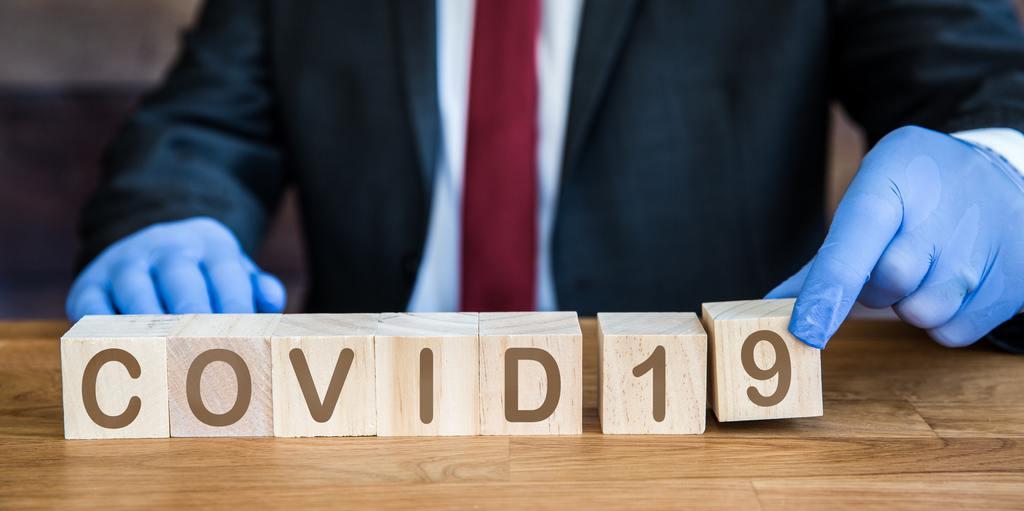 a male wearing ppe blue gloves and spelling the word covid 19 in wooden blocks in a coronavirus | Plantech | Σύμβουλοι Επιχειρήσεων | Κατασκευή Ιστοσελίδων | Ιωάννινα